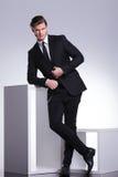 Geschäftsmann, der auf einem Würfel sich lehnt Stockfotos
