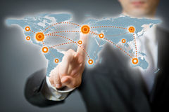 Geschäftsmann, der auf einen Punkt auf einer Weltkarte zeigt Stockfotografie