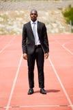 Geschäftsmann, der auf einer laufenden Bahn steht Stockbild