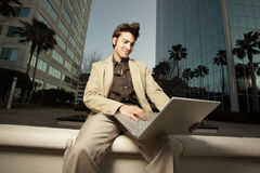 Geschäftsmann, der auf einer Leiste sitzt stockbild