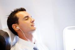 Geschäftsmann, der auf Flugzeug sich entspannt Stockfoto