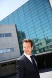 Geschäftsmann, der auf Front des Bürogebäudes steht Lizenzfreies Stockfoto