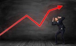 Geschäftsmann, der auf Fußbodenbrett steht und in Furcht unter hellen roten Statistikpfeil verbiegt lizenzfreie stockbilder