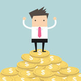 Geschäftsmann, der auf Goldmünze steht Lizenzfreies Stockfoto