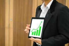 Geschäftsmann, der auf grünes Balkendiagramm zeigt Stockfotos