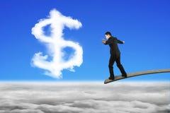 Geschäftsmann, der auf hölzernem Brett mit Dollarzeichen-Form Clo balanciert Lizenzfreie Stockbilder