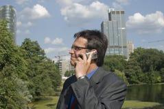Geschäftsmann, der auf Handy alking ist Stockfoto