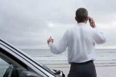 Geschäftsmann, der auf Handy in dem Meer spricht stockfotos