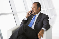 Geschäftsmann, der auf Handy in der Vorhalle spricht Stockbilder