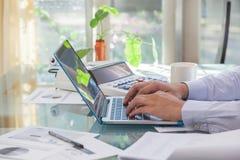 Geschäftsmann, der auf Laptoptastatur während von zu Hause arbeiten schreibt Lizenzfreie Stockfotos