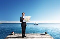 Geschäftsmann, der auf Pier mit Karte steht Lizenzfreies Stockbild