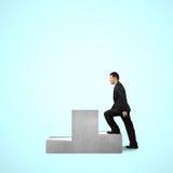 Geschäftsmann, der auf Podium klettert Stockfoto