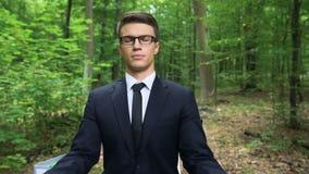 Geschäftsmann, der auf Schreibtisch sitzt und in der Frischluft im Wald, Inspiration meditiert stock video footage