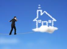 Geschäftsmann, der auf Seil in Richtung zur Hausformwolke im Himmel geht Stockfoto