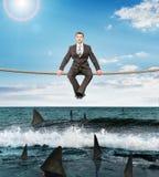 Geschäftsmann, der auf Seil sitzt lizenzfreie stockfotografie