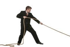 Geschäftsmann, der auf Seil zieht Stockfoto