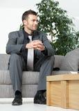 Geschäftsmann, der auf Sofa sitzt Stockfotos
