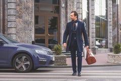 Geschäftsmann, der auf Straße mit Aktenkoffer geht lizenzfreies stockbild