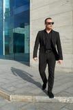 Geschäftsmann, der auf Straße nahe dem Büro geht Stockfoto