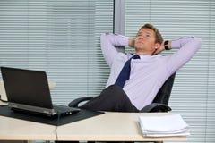 Geschäftsmann, der auf Stuhl mit Laptop auf Schreibtisch sich entspannt Lizenzfreies Stockbild