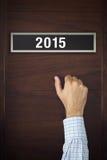 Geschäftsmann, der auf Tür mit Nr. 2015 klopft Stockbild