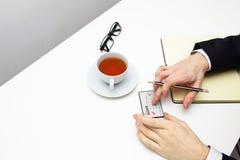 Geschäftsmann, der auf Taschenrechner mit Tasse Tee auf weißem Hintergrund zählt Lizenzfreies Stockfoto
