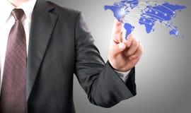 Geschäftsmann, der auf Weltkarte zeigt Lizenzfreie Stockbilder