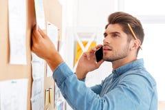 Geschäftsmann, der Aufgabenbrett betrachtet und am Telefon spricht Stockbild