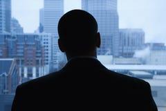 Geschäftsmann, der aus Fenster heraus schaut Stockbilder