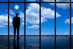 Geschäftsmann, der aus hohem Aufstiegsbürofenster heraus hellem Sonnenschein des blauen Himmels und weißen Wolken betrachtet. Lizenzfreies Stockbild