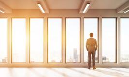 Geschäftsmann, der aus panoramischem Fenster heraus in Großstadt aufpasst Lizenzfreie Stockbilder