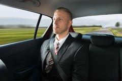Geschäftsmann, der in Auto reist Stockfotos