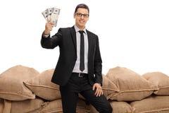 Geschäftsmann, der Bündel Geld vor Leinwandsäcken hält Stockfotos