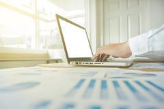 Geschäftsmann, der am Büro mit Laptop und an den Dokumenten auf seinem arbeitet Lizenzfreies Stockbild