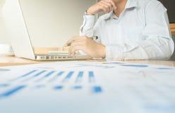 Geschäftsmann, der am Büro mit Laptop und an den Dokumenten auf seinem arbeitet Stockfoto