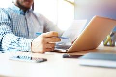 Geschäftsmann, der am Büro mit Laptop und an den Dokumenten auf seinem Schreibtisch arbeitet