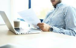 Geschäftsmann, der am Büro mit Laptop und an den Dokumenten auf seinem Schreibtisch arbeitet Stockfoto