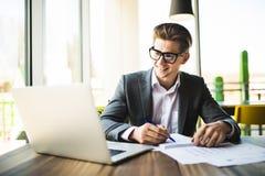 Geschäftsmann, der am Büro mit Laptop und an den Dokumenten auf seinem Schreibtisch arbeitet Lizenzfreie Stockfotografie