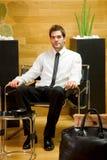 Geschäftsmann, der in Bürovorhalle wartet Stockbild