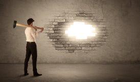 Geschäftsmann, der Backsteinmauer mit Hammer schlägt und ein Loch öffnet Stockfotografie