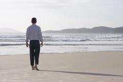 Geschäftsmann, der barfuß auf einen Strand geht Stockfotografie