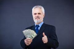 Geschäftsmann, der Bargeld anhält und sich Daumen zeigt Stockfotografie