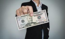 Geschäftsmann, der Bargeld, für das Neigen und usw. zeigt Lizenzfreies Stockfoto