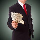 Geschäftsmann, der Bargelddollar hält Stockbilder