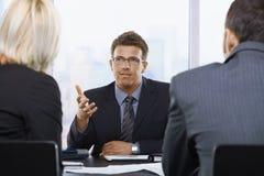Geschäftsmann, der bei der Sitzung spricht Lizenzfreies Stockfoto