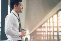 Geschäftsmann, der bei Gebäudegehwegfirma mit Hoffnungskonzept steht stockfoto