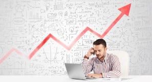 Geschäftsmann, der bei Tisch mit Marktdiagrammen sitzt Lizenzfreie Stockfotos