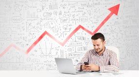 Geschäftsmann, der bei Tisch mit Marktdiagrammen sitzt Stockfoto