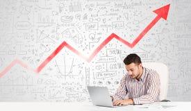 Geschäftsmann, der bei Tisch mit Marktdiagrammen sitzt Lizenzfreies Stockbild