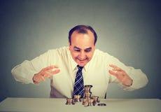Geschäftsmann, der bei Tisch sitzt, sein Geld betrachtend, das sie mit den Händen schützt Stockfotografie